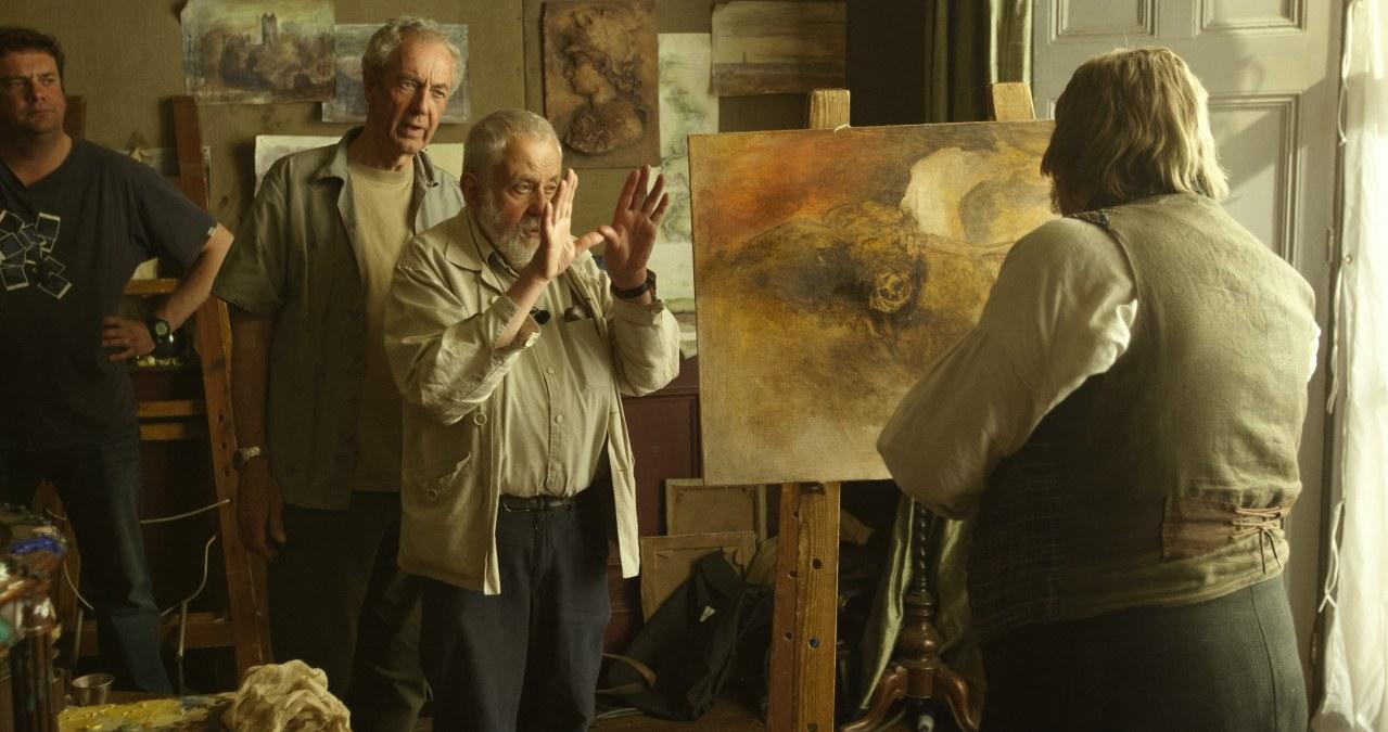 MR. TURNER – MEISTER DES LICHTS: Regisseur Mike Leigh und Schauspieler Timothy Spall stehen vor einer Staffelei. Der Regisseur gibt Spall Anweisungen.