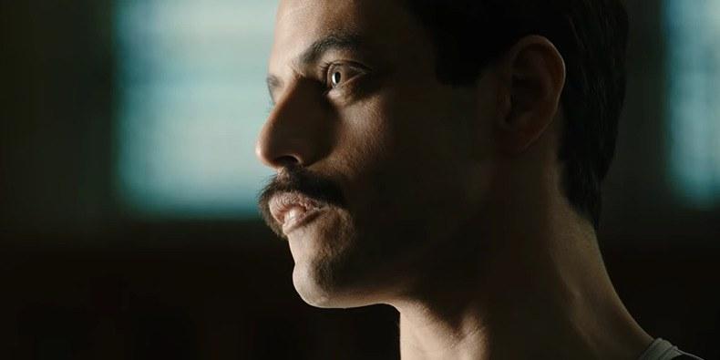 Rami Malek steht als Freddie Mercury in BOHEMIAN RHAPSODY vor einem grünlich-schwarz schimmernden Hintergrund.